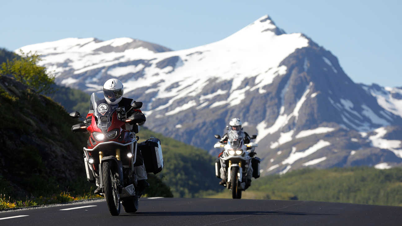 Two bikes riding down the road with the snow capped mountains in the distance.