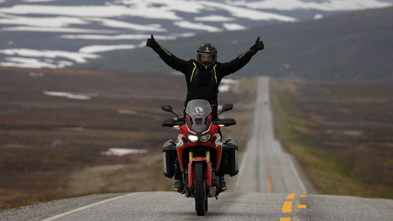 Man on a Honda Africa Twin with his arms raised high on the roads in Nordkapp.