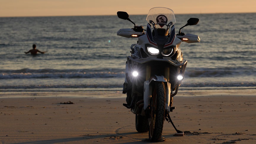 Honda Africa Twin parked up on the sand with a man in the sea in the distance.
