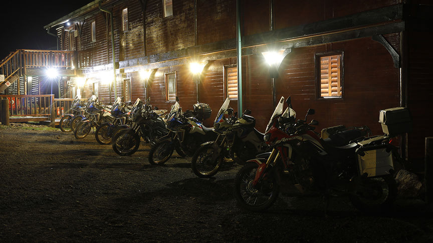 A row of Honda Africa Twin's parked outside a roadside destination at night.