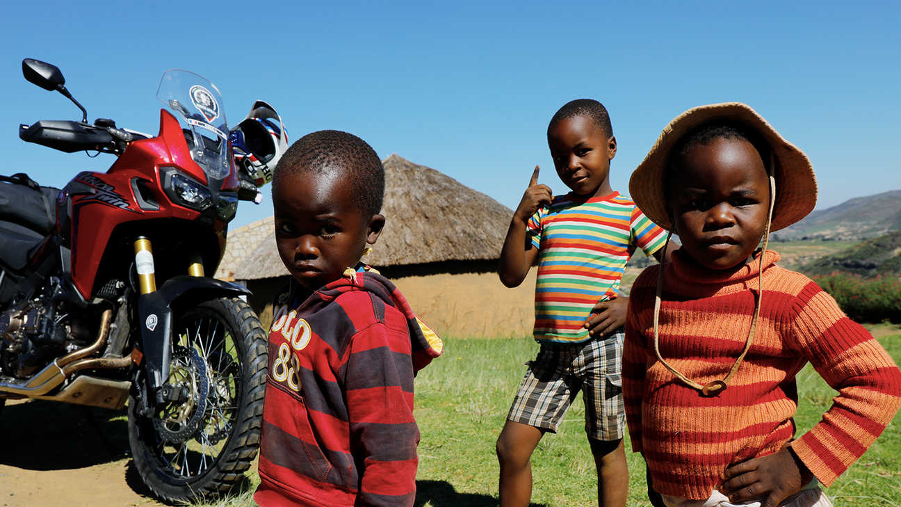 Young children outside gathered around a CRF1000L Africa Twin.