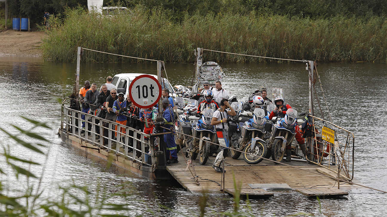 Bikes being transported across a river on a boat.