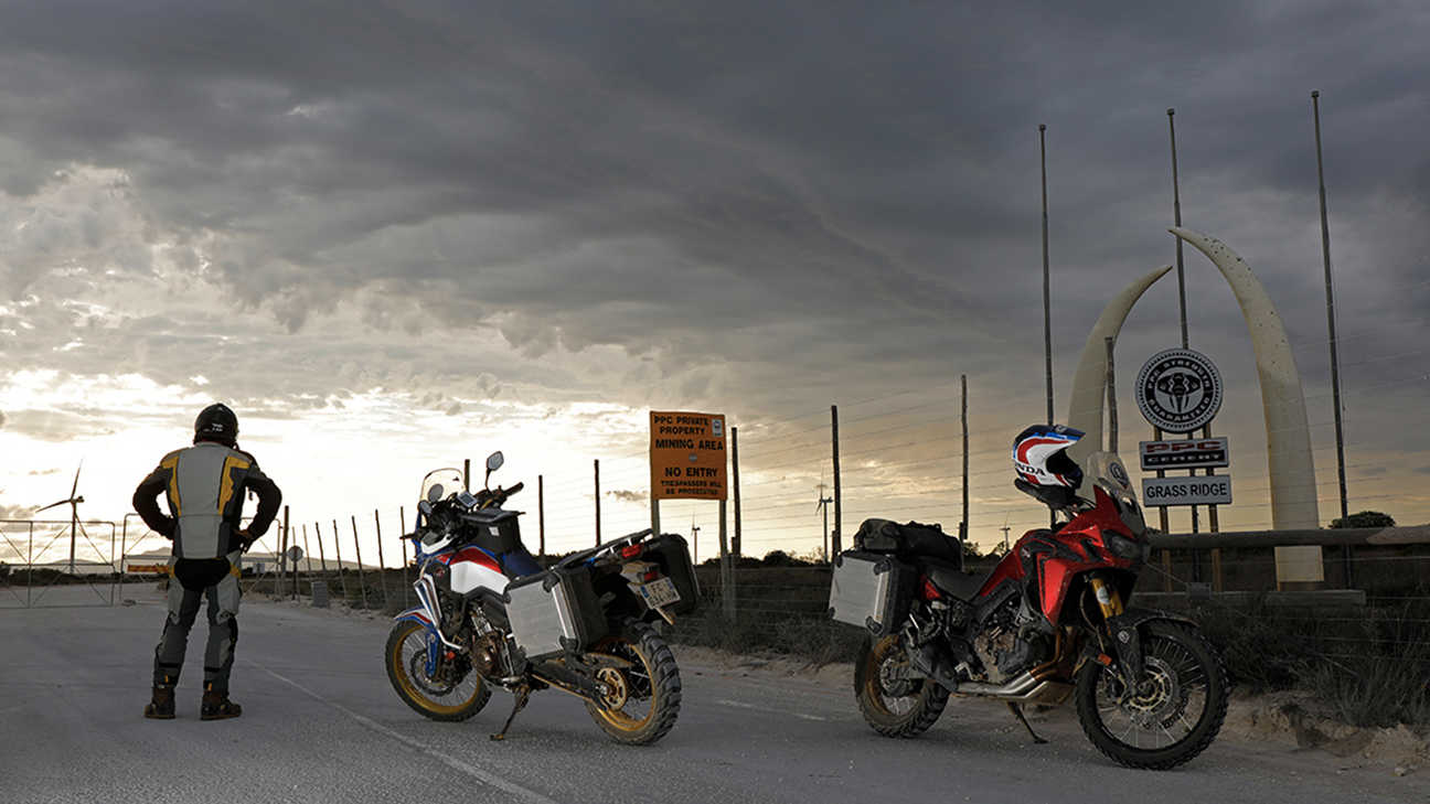 Rider looking out to the horizon standing next to two Africa Twin's parked up on the tarmac.
